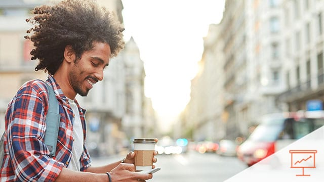 Person checking their phone while drinking coffee